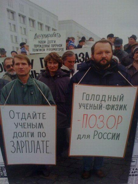 """I cartelli dei protestanti dicono """"Un fisico affamato è una vergogna per la Russia"""" e """"Date agli scienziati gli stipendi che si meritano""""."""