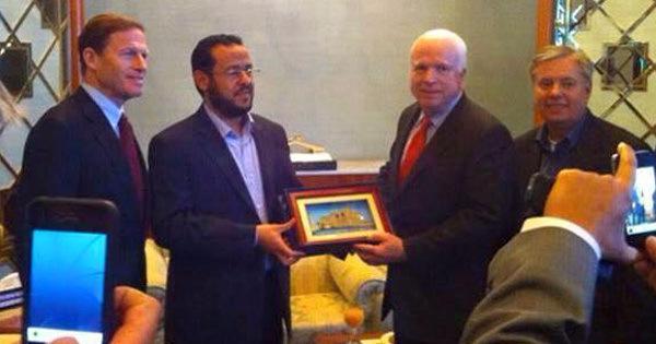 Immagine: Membri del Congresso degli Stati Uniti posano insieme ad un comandante di Al-Qaeda dopo che la NATO nel 2011 ha distrutto il paese e lo ha consegnato a dei terroristi dichiarati.